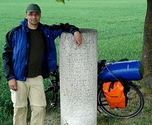 Meilenstein auf der Via Claudia Augusta. Bild mit Felix und Fahrrad am Meilenstein